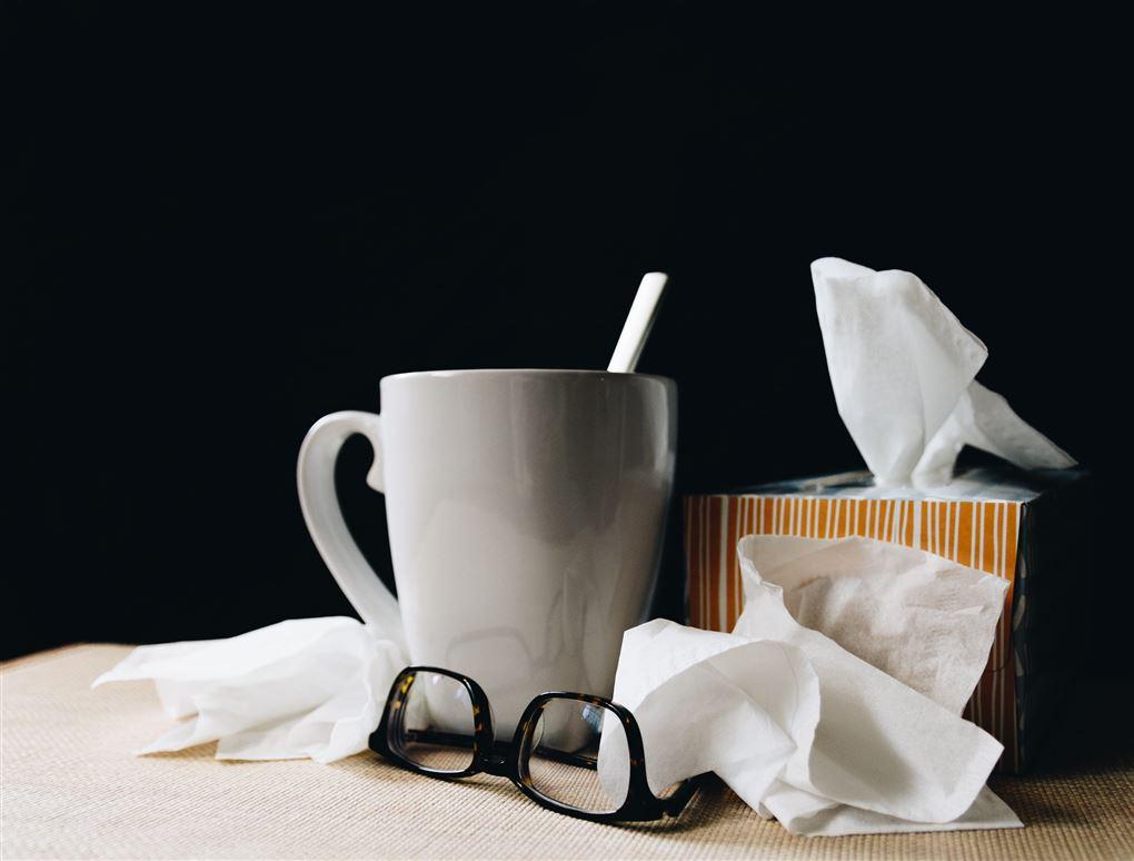 kop med te, briller og lommetørklæder står på natbord