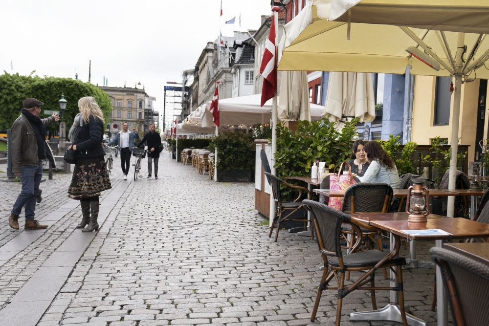 En gade med mange mennesker og flere cafeer med borde udenfor.
