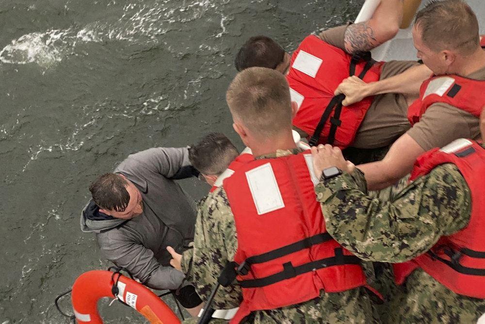 En overlevende på vej op i en båd