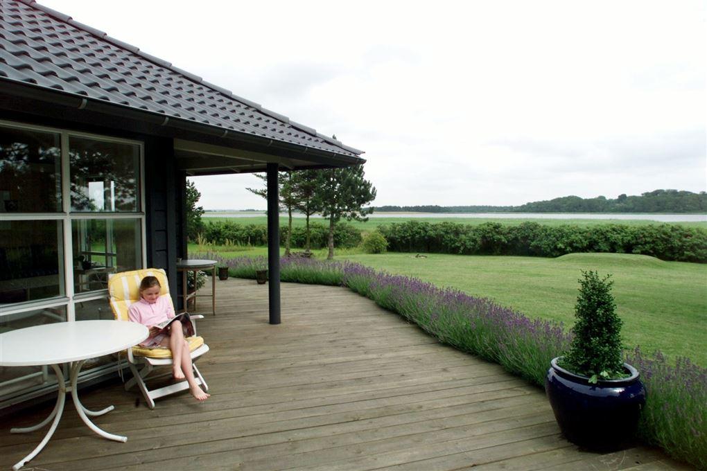 En pige sidder og læser en bog på en terrasse i et sommerhus