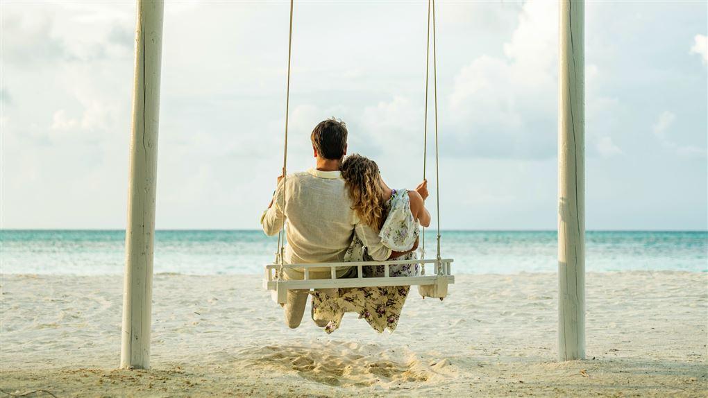 Par ses i gynge på stranden