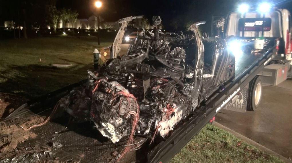 udbrændt bil ligger på ladet af en lastbil
