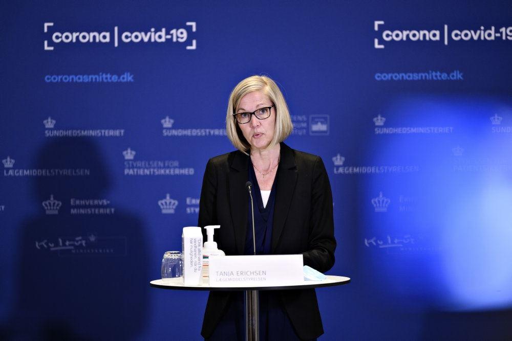 kvinde står foran bord til på pressemøde