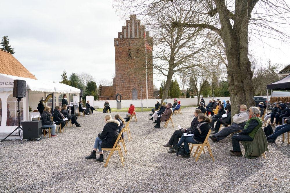 folk holder gudstjeneste udenfor en kirke