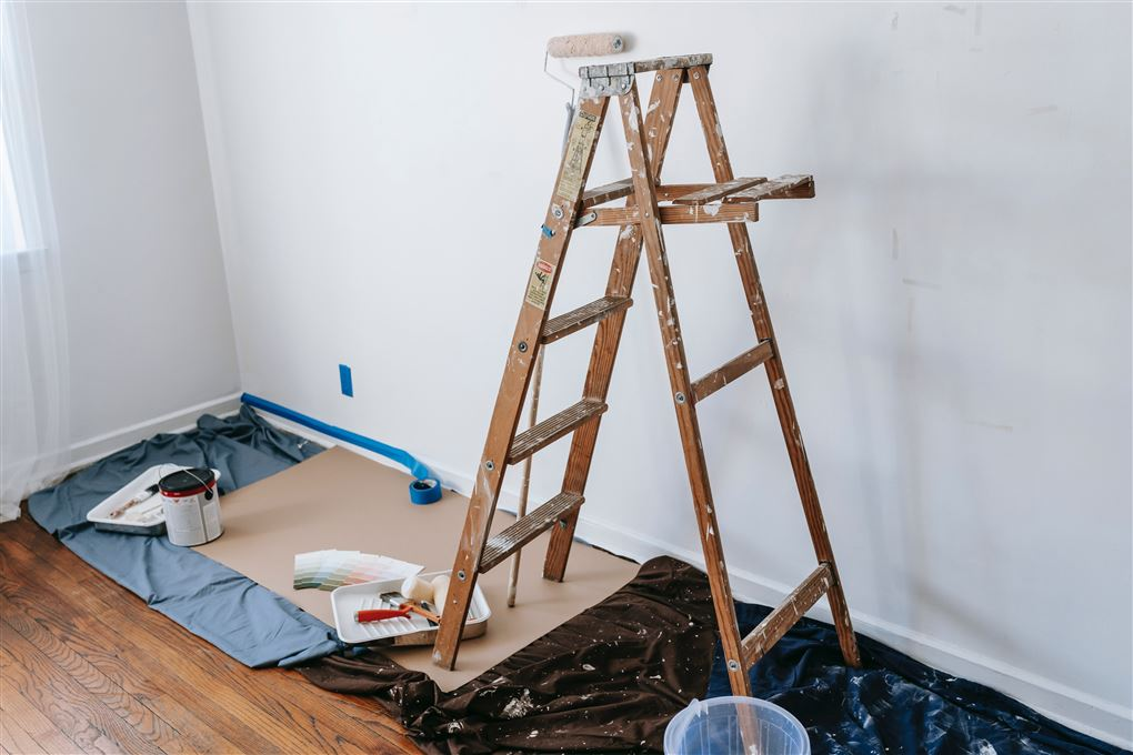 Stige og malerbøtter ved væg