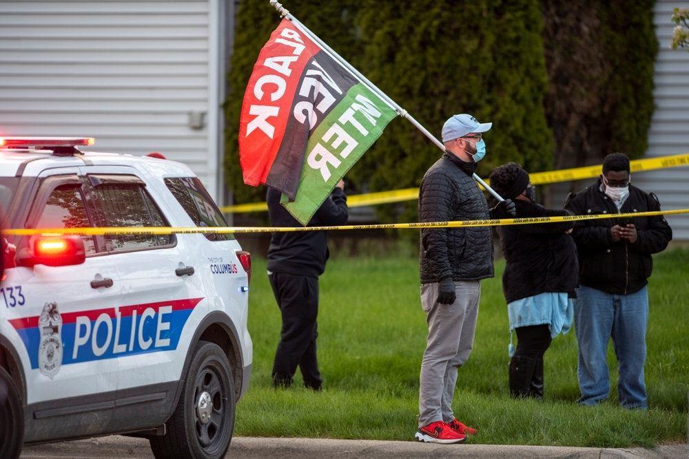 politibil holder ved siden af mand med banner