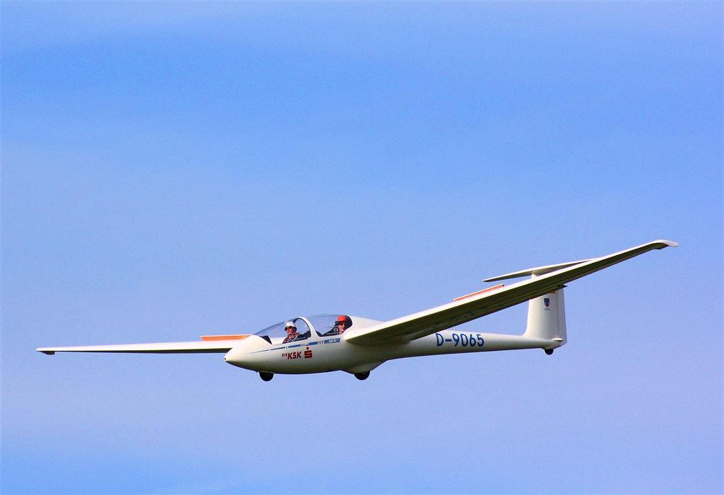 En svæveflyver i luften med to personer om bord