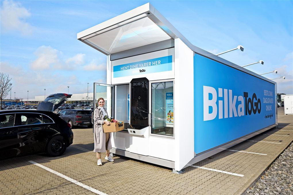 Kvinde med papkasse ved Bilka-container