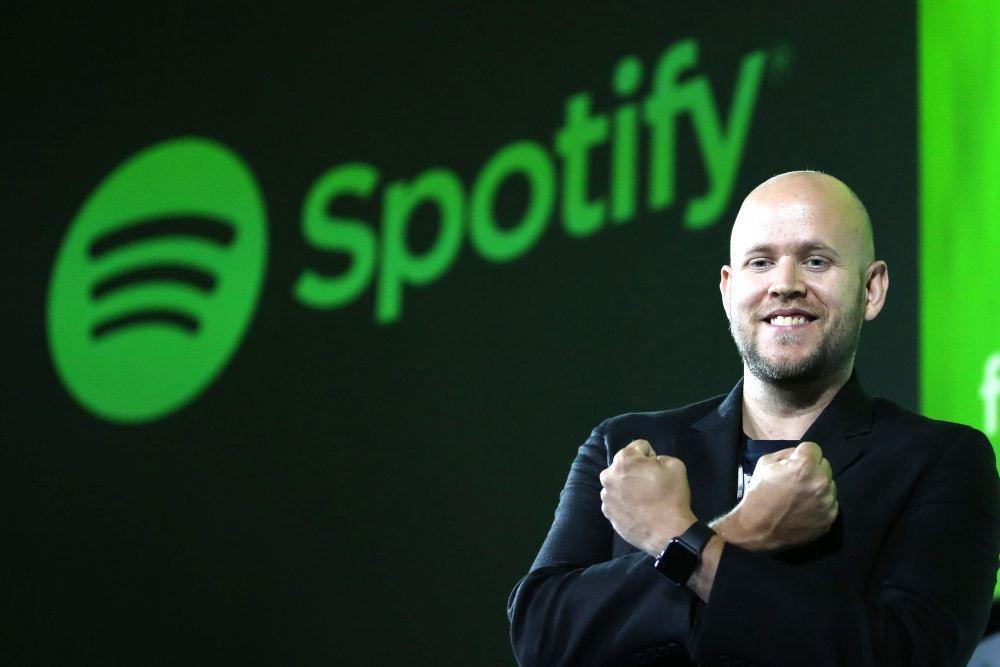 En glad mand foran Spotify-logo