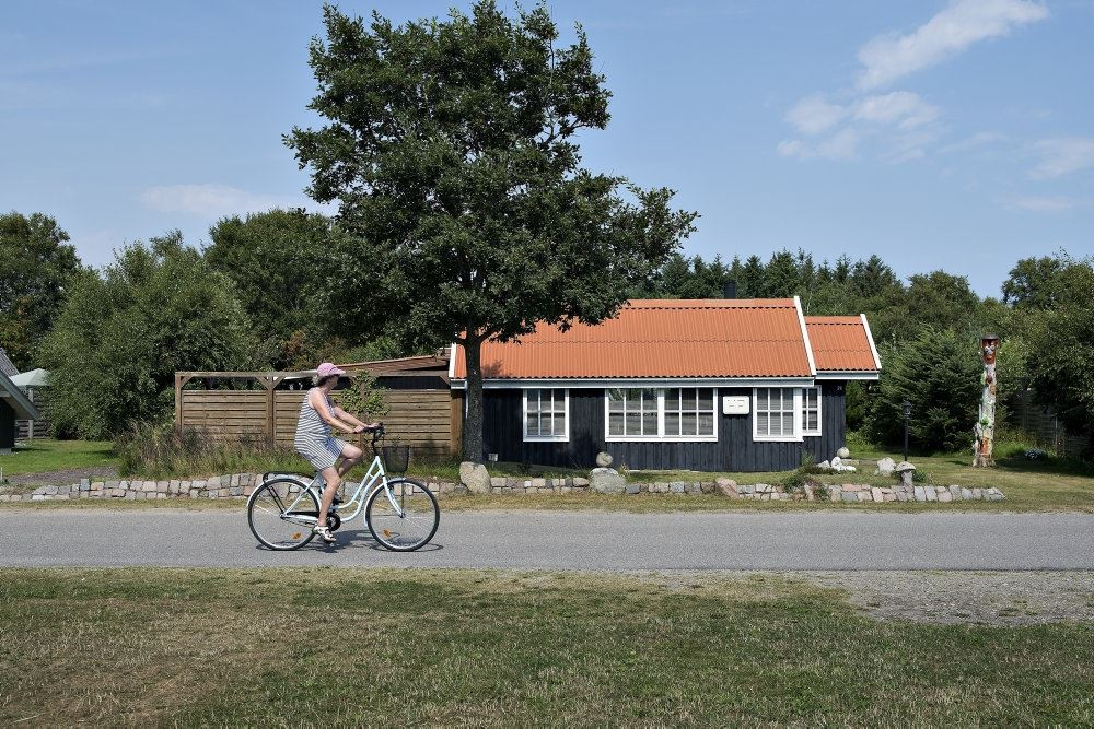 person cykler forbi sommerhus