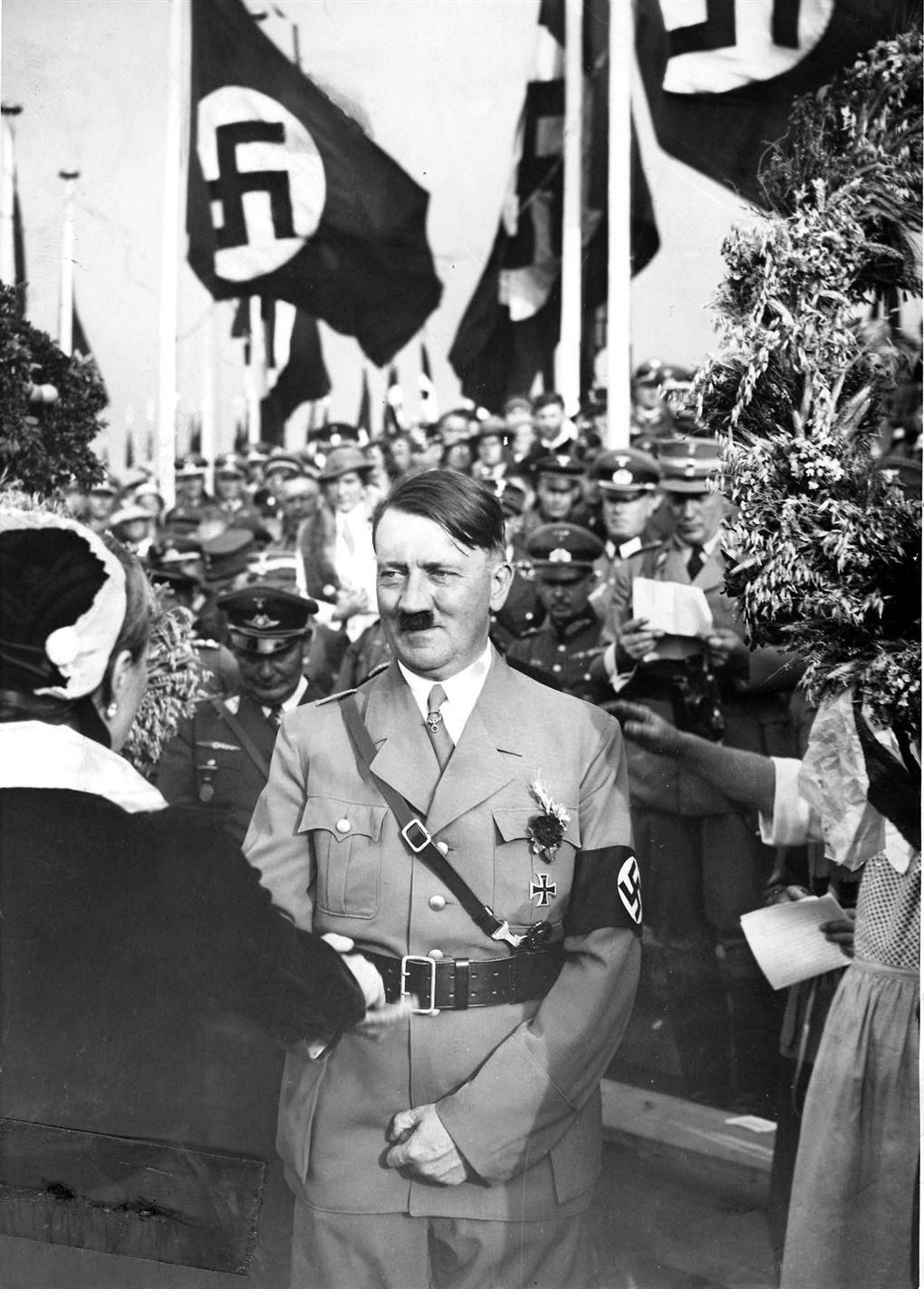 Adolf Hitler smiler smørret under det velkendte lille overskæg.