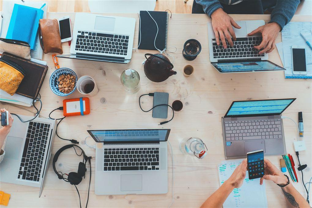 Rodet skrivebord fyldt med computere.