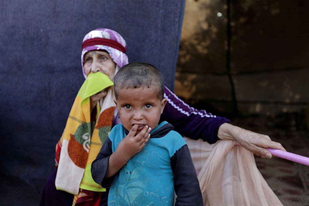 En syrisk lille dreng og gammel dame i en lejr
