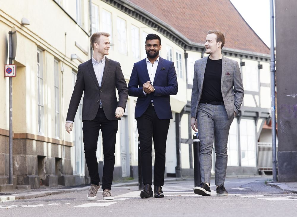 tre mænd går ned ad gaden i jakkesæt