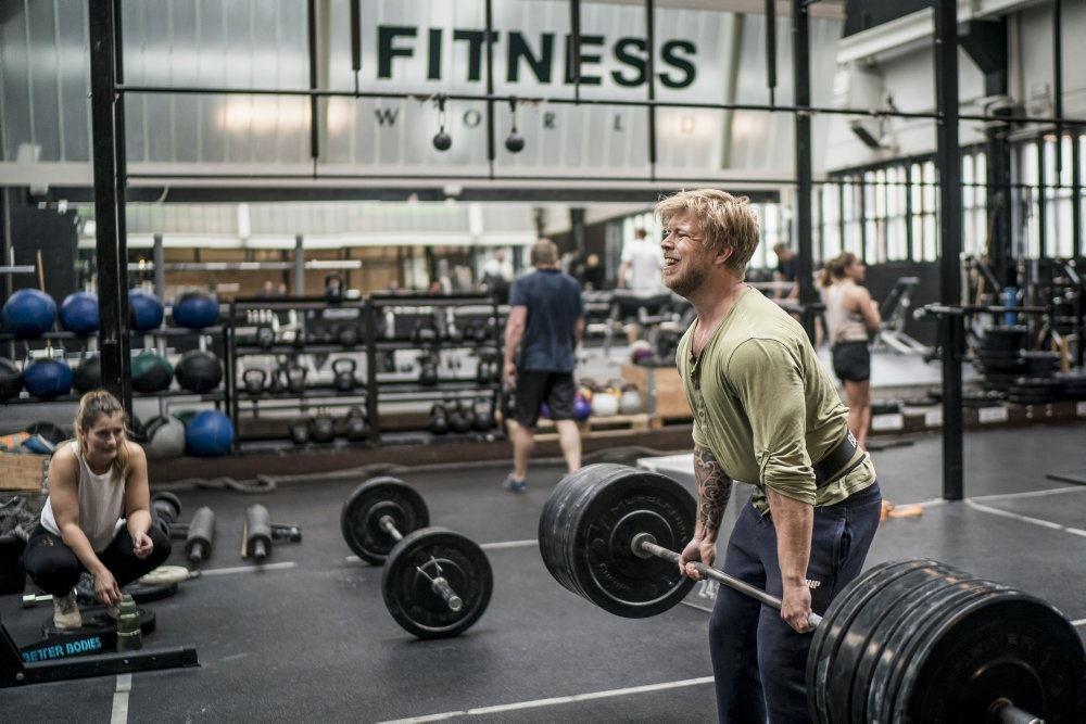 mand løfter jen i fitnesscenter