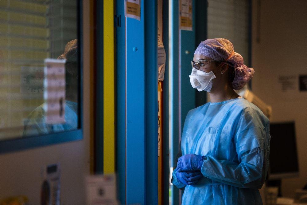 en sygeplejerske i blåt med mundbind