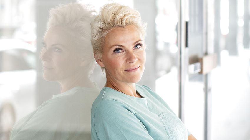 Lene Beier med det meget genkendelige korte lyse hår. Hun er fotograferet med ryggen mod en rude, som på den måde viser hende spejlvendt. Hun er iført en mintgrøn trøje.