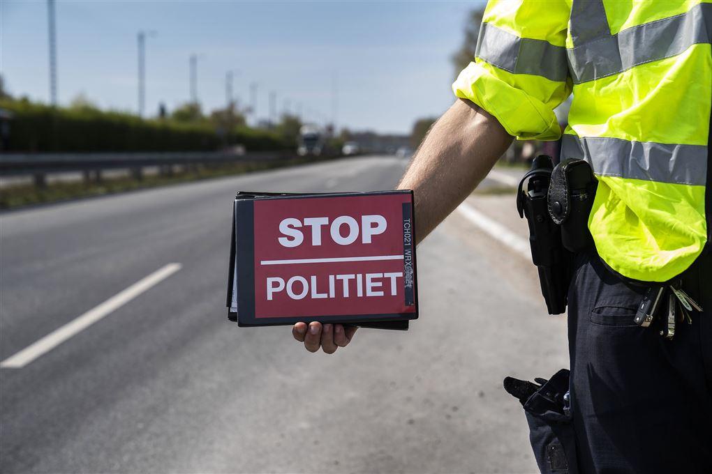 politimand holder rødt stopskilt