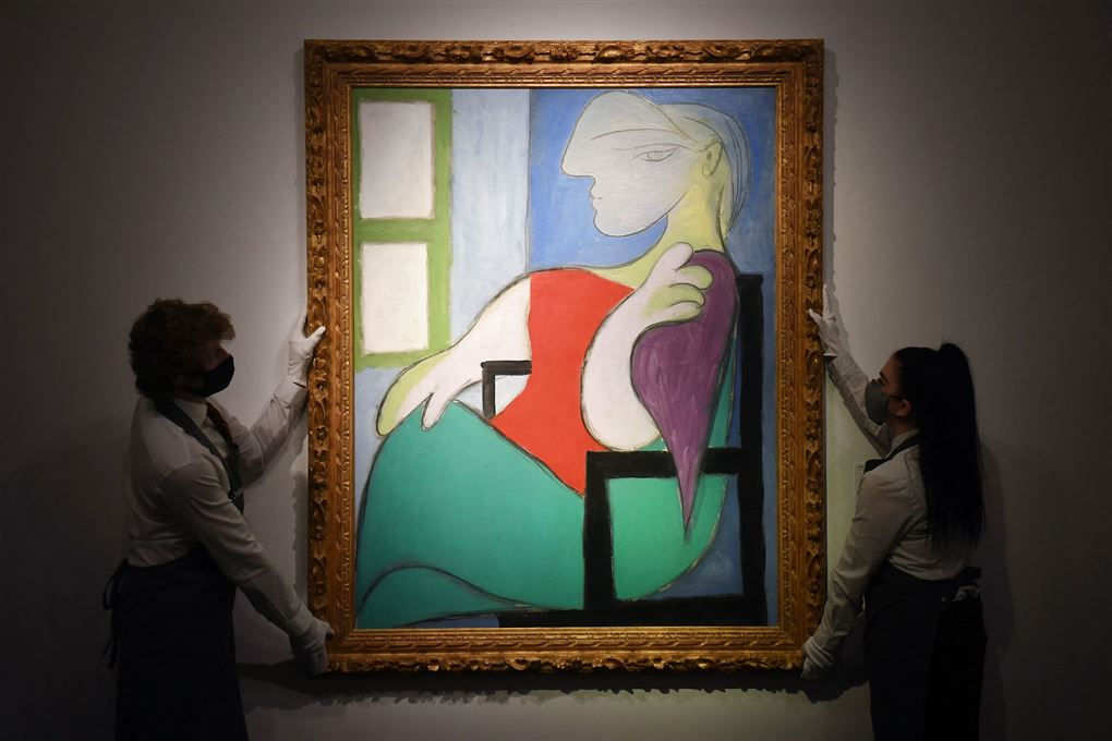 Et farverigt maleri af Picasso holdes i hver sin ramme af to kvinder