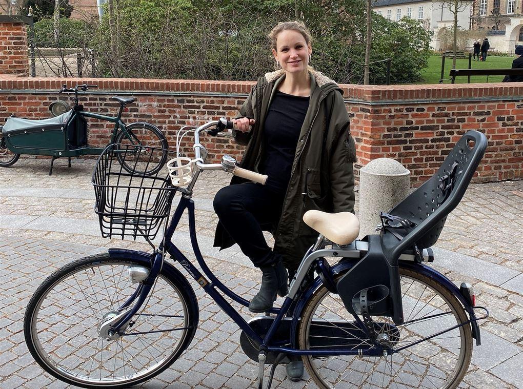 En smilende dame ved sin cykel