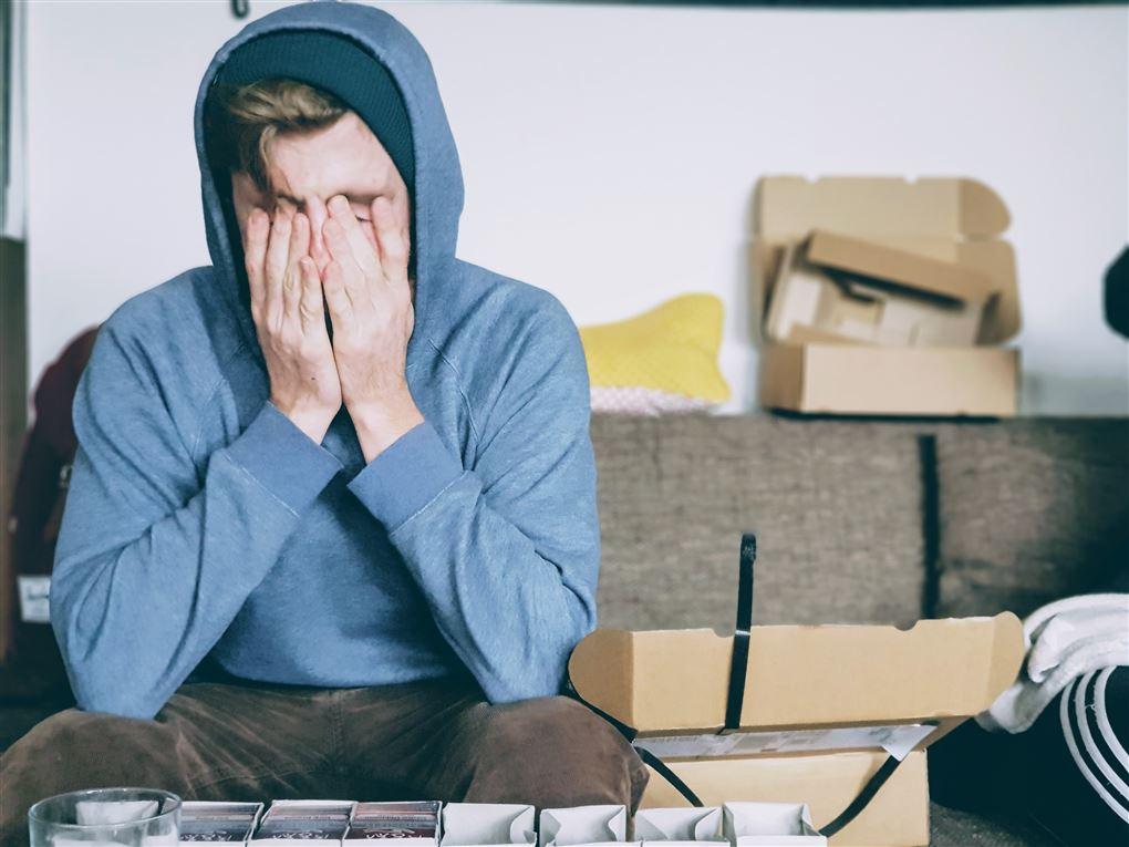 En ung mand sidder i en sofa omgivet af papkasser og holder sig for ansigtet.