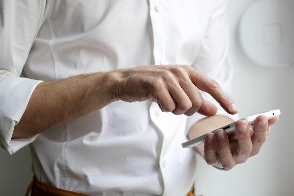 mand trykker på mobiltelefon