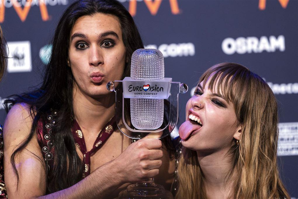 En kvinde rækker tunge og en mand holdet et trofæ