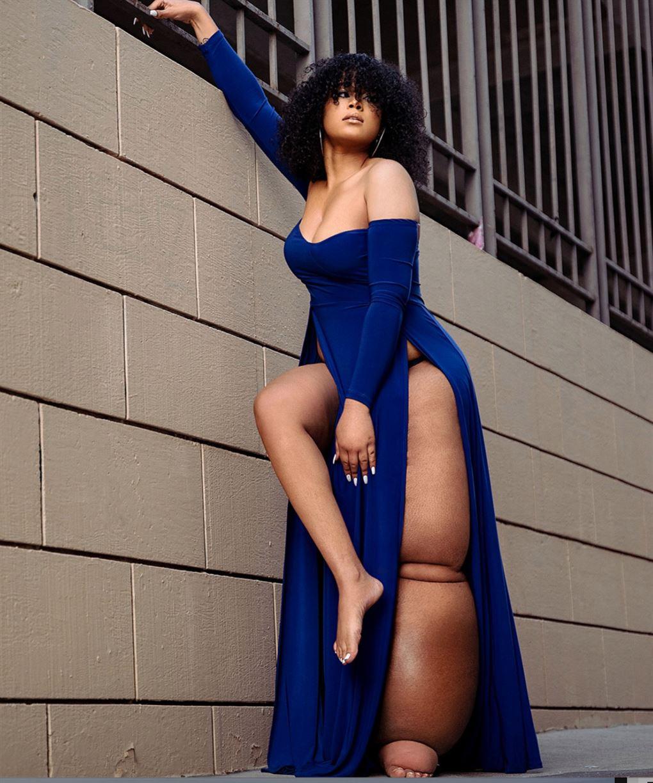 En smuk mørk pige i en blå kjole med et kæmpeben