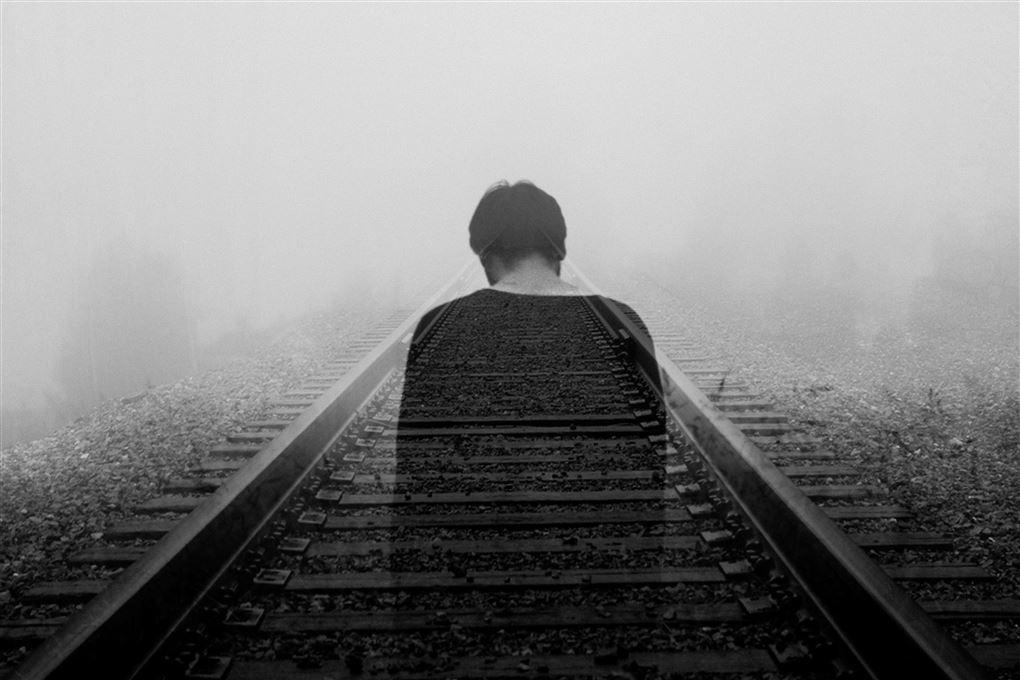 En mand kigger trist ned på nogle jernbanespor