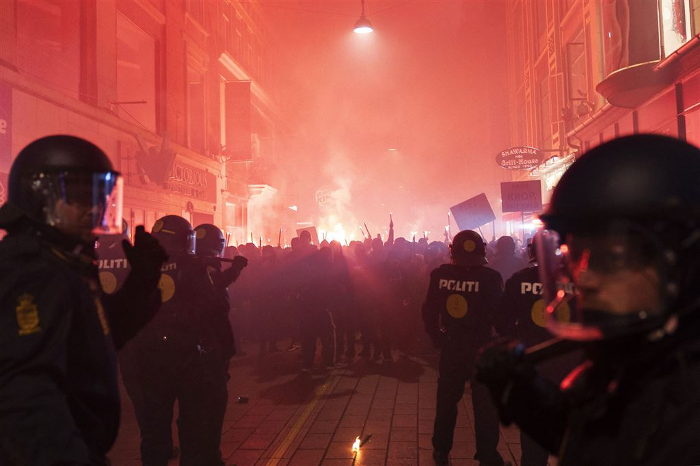 politibetjente står ved demonstration med fakler