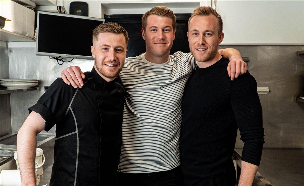 Tre yngre mænd der smiler i et stort køkken