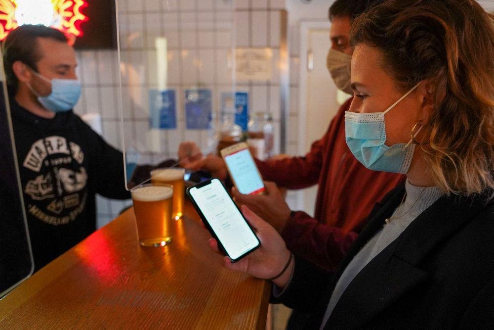 Folk i en bar med mundbind og smartphones åbne