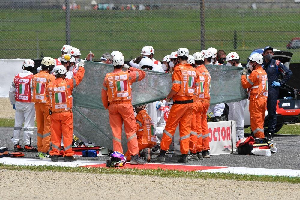 Mænd i orange tøj skærmer af ved en ulykke på en bane