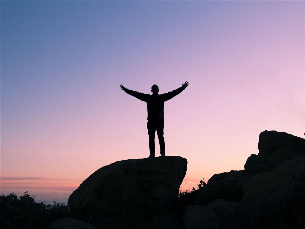 En mand rækker armene i vejret på en klippe i solnedgang