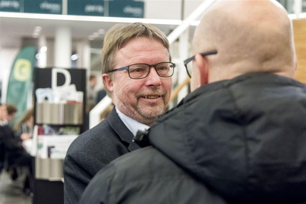 Politiker Niels Dueholm hilser på en mand med et smil.