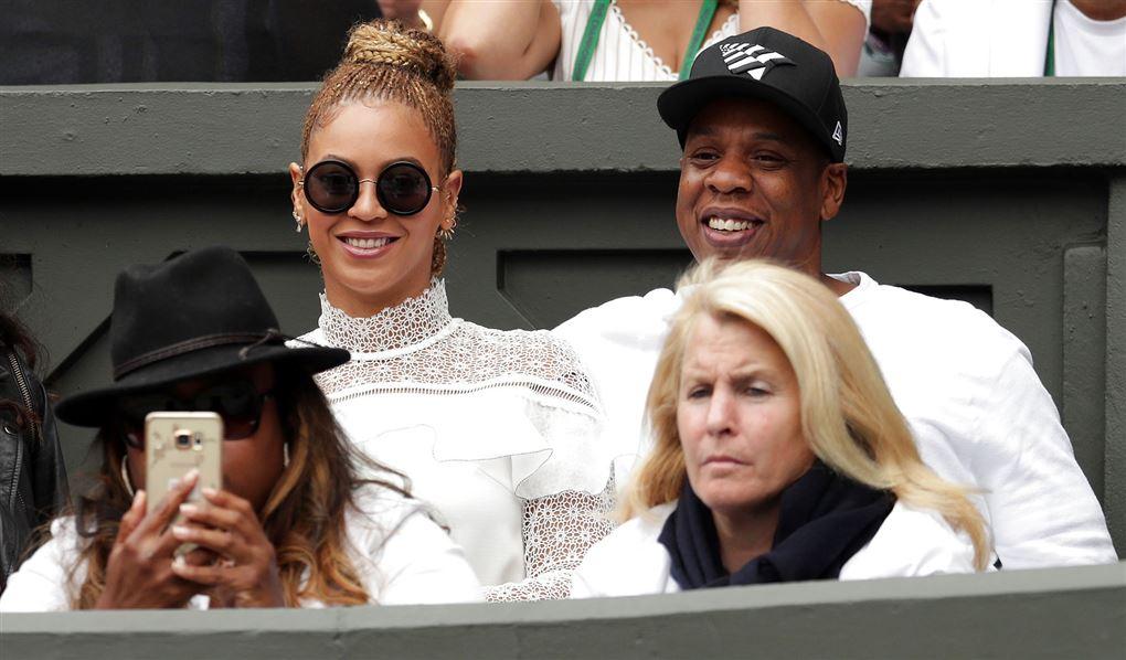 Beyoncé og Jay Z til en tenniskamp. De er begge klædt i hvidt og hun har store solbriller på.