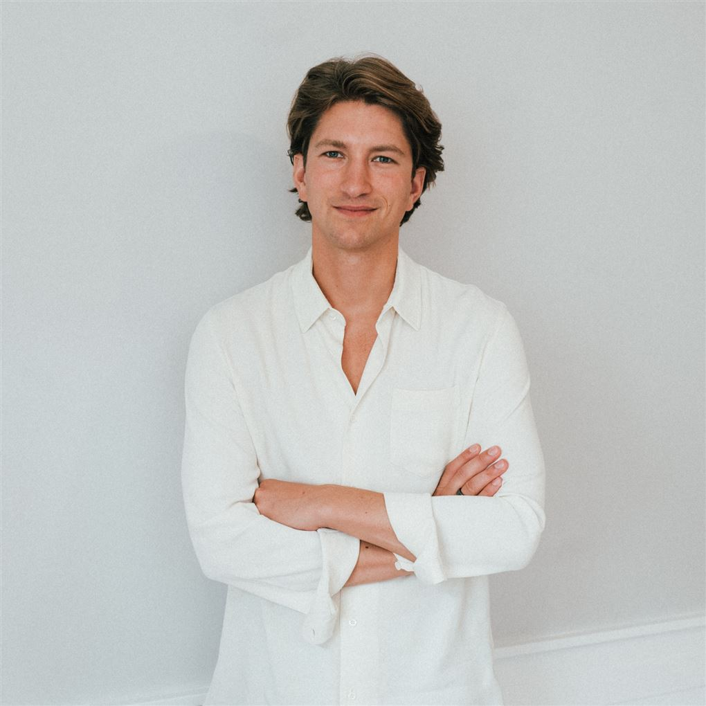 En smilende yngre mand i hvid skjorte