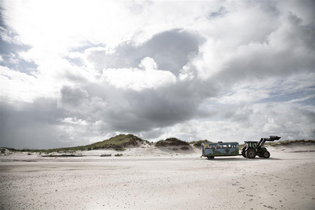 idyllisk billede af traktor med vogn på strand
