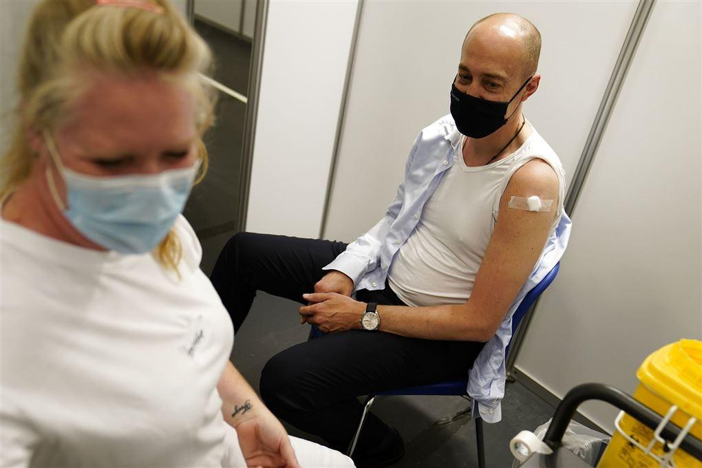 Magnus Heunicke med den ene arm ude af trøjen og et plaster på skulderen efter vaccinationen