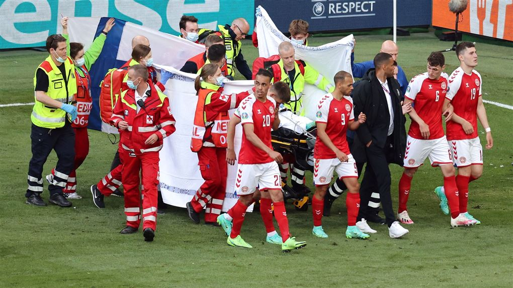 Eriksen bæres fra banen og skærmes af de danske spillere