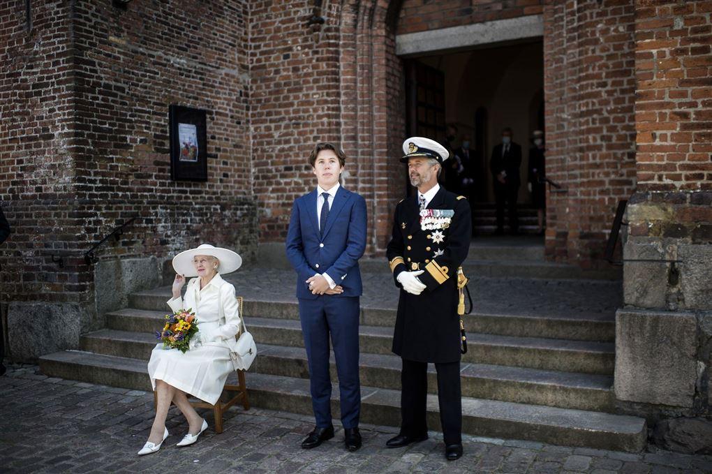 Dronningen sidder på en stol foran en kirke ved siden af hende står prins Christian og ved siden af ham står kronprins Frederik, der er i uniform