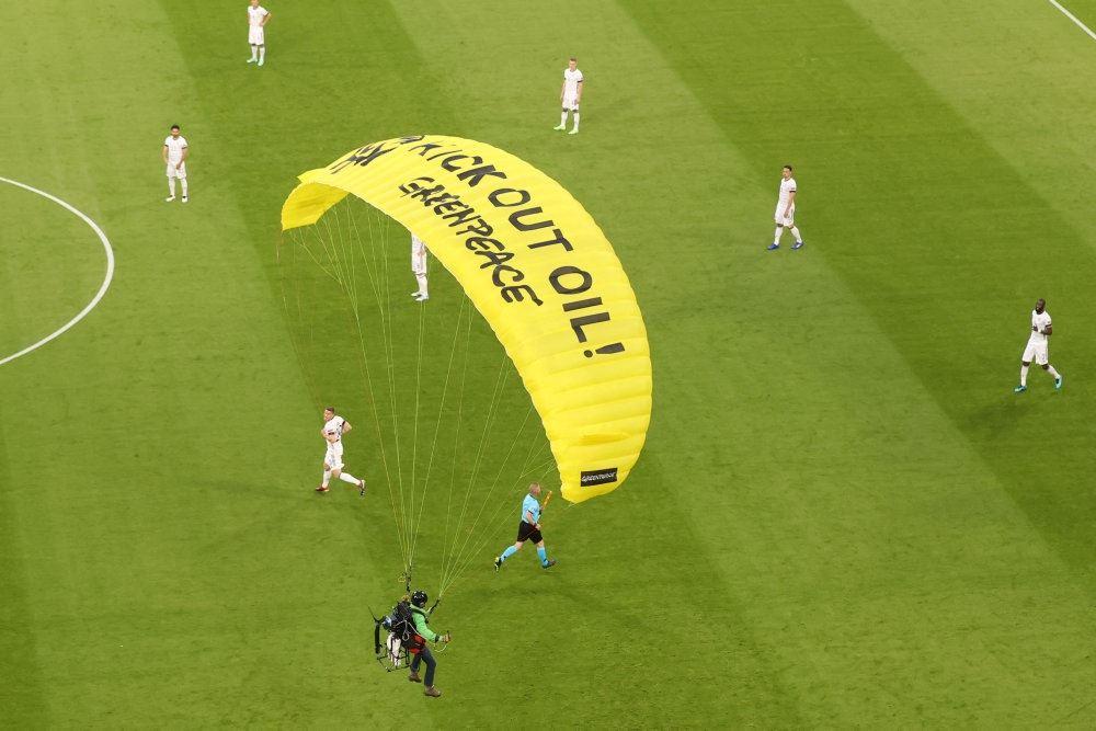 faldskærmsudspringer lander på bane under fodboldkamp