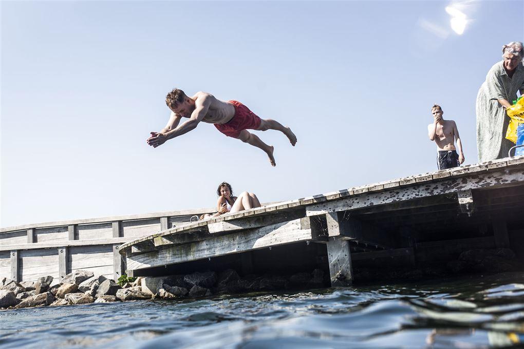 Mand springer i vandet.