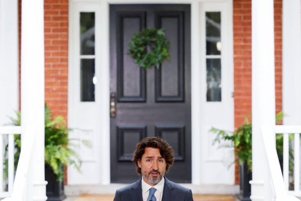 En skægget mand foran en trappe til en orange bygning