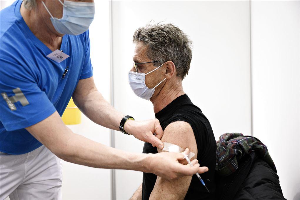 mand får vaccination med et stik i skulderen