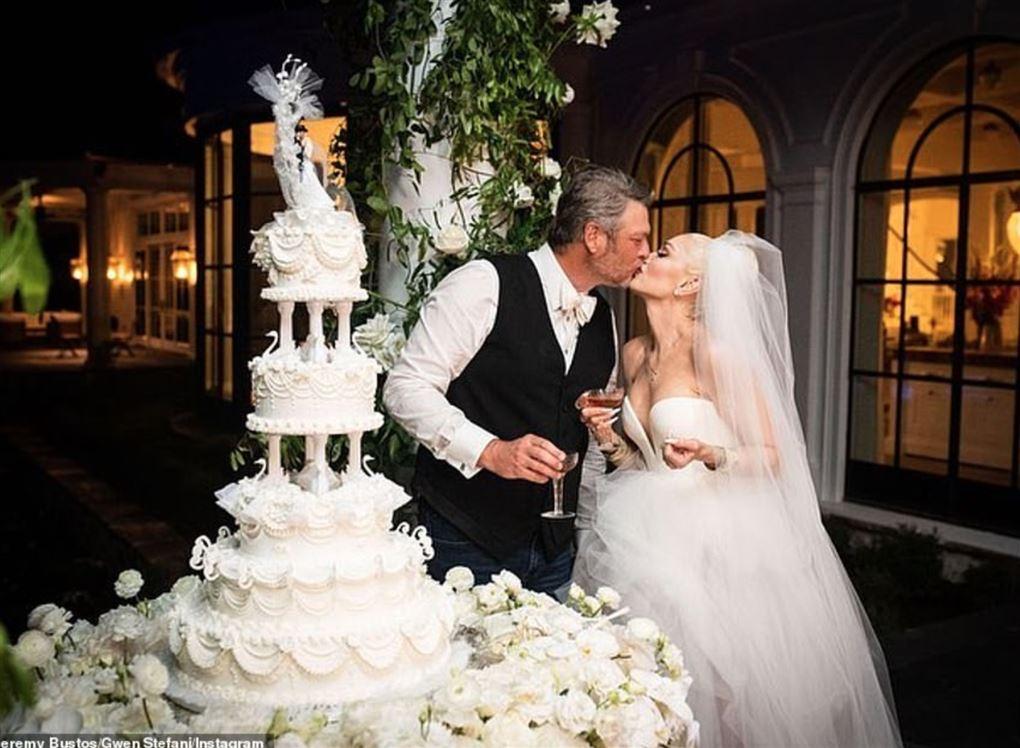Et ægtepar kysser hinanden foran en kæmpe kage