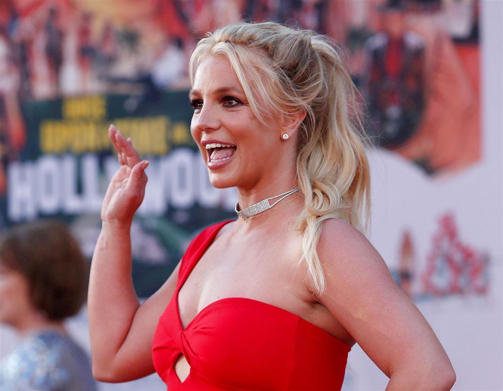 En blond kvinde i en rød kjole vinker
