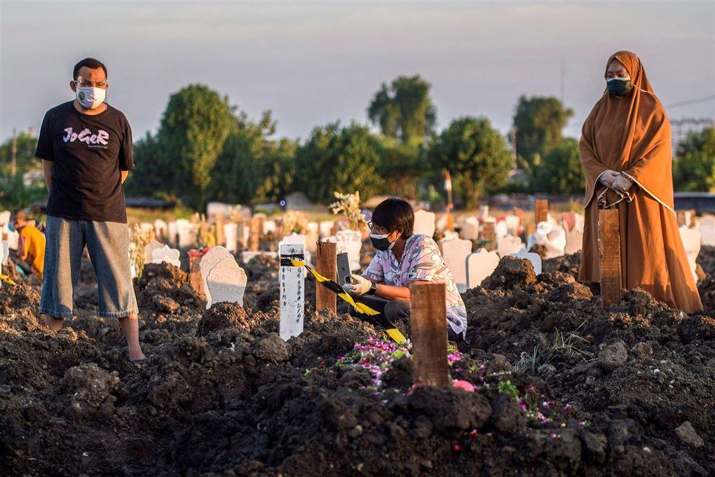 En mor, far og søn på en kirkegård