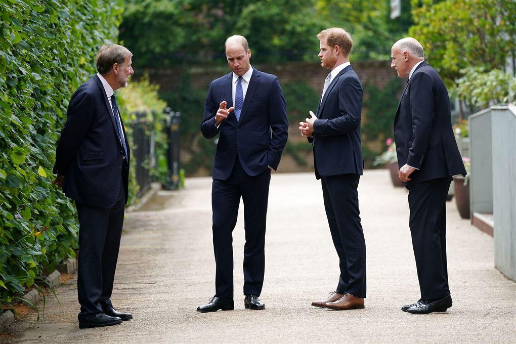 Fire mænd i jakkesæt - den ene med brune sko.