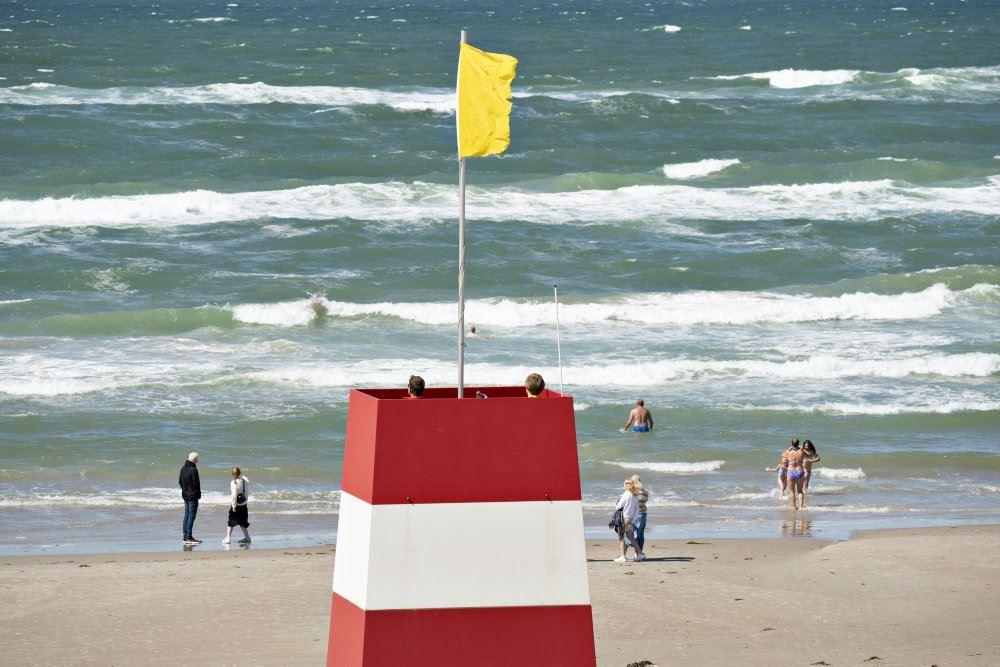 Et livreddertårn med gult flag på en strand